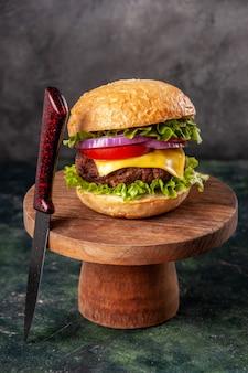空きスペースのある暗いミックス色の表面に木の板においしいサンドイッチと赤いフォーク