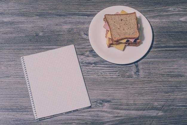 灰色の木製の背景にノートブックと丸い白いプレート上のおいしいサンドイッチ。上面図。ヴィンテージ効果。