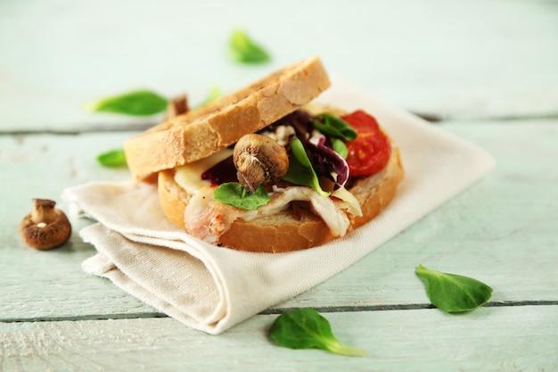 木製のテーブルの上のおいしいサンドイッチ、クローズアップ
