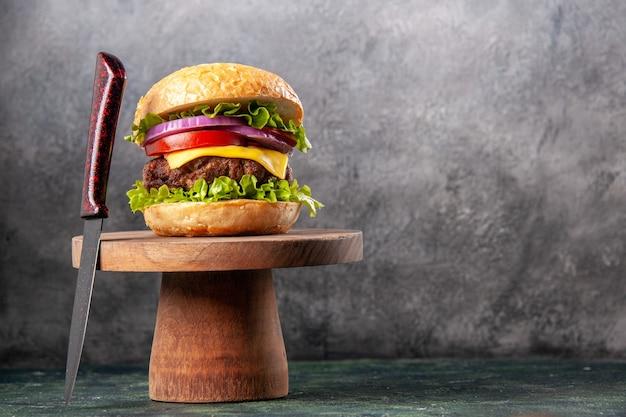 Panino gustoso e forchetta rossa su tagliere di legno su superficie di colore misto scuro