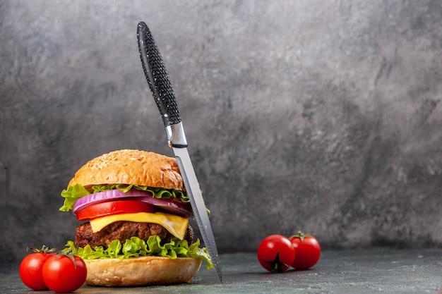 フリースペースのある暗いミックスカラーの表面に茎のナイフを入れたおいしいサンドイッチトマト