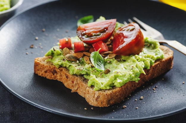 Tasty sandwich on wholegrain bread with mashed avocado and tomatoes