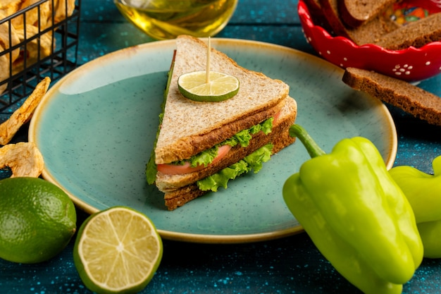 Tasty sandwich with green salad ham and tomatoes as a filling along with lemon and oil on blue