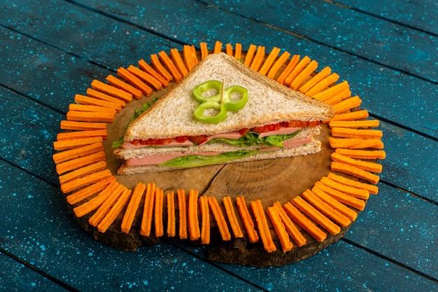 Gustoso panino con insalata verde prosciutto e pomodori come ripieno insieme a fette biscottate all'arancia sul blu