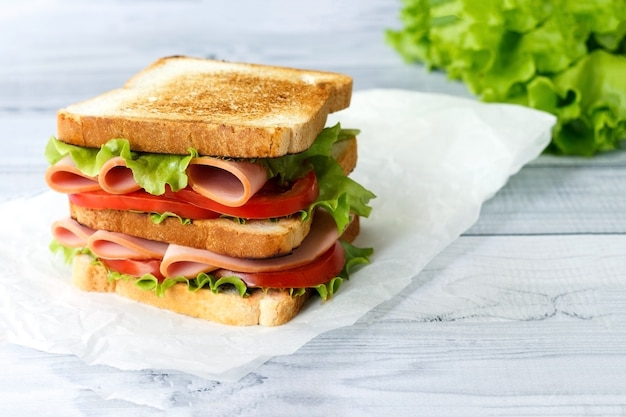 Tasty sandwich with ham salad and tomatoes on light surface