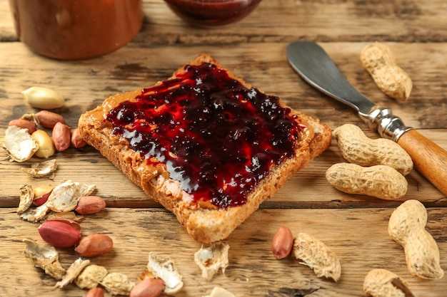 Tasty sandwich with peanut butter and jam on table