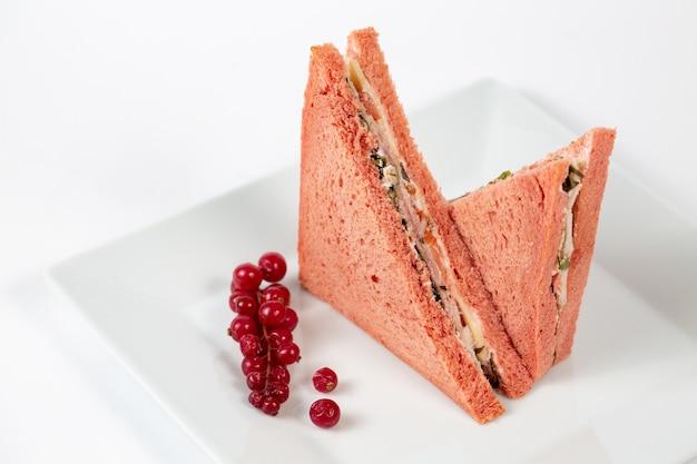 白いプレートにピンクのパンとおいしいサンドイッチ
