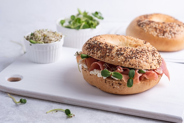 Tasty sandwich with prosciutto cheese and microgreens for breakfast, cutting board with ham and ricotta bagels on a white background.