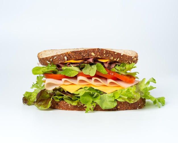 Tasty sandwich with vegetables, ham and cheese
