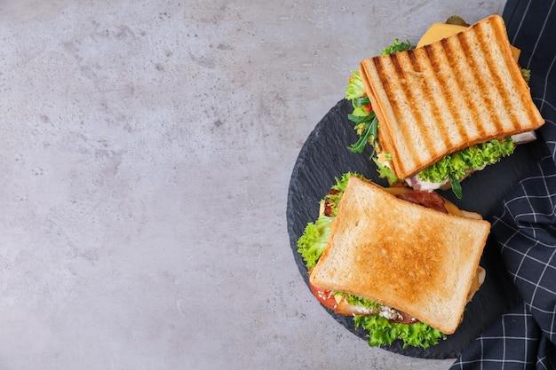 Вкусные бутерброды служили на сером столе, вид сверху. место для текста