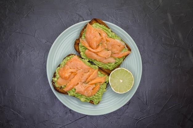 Вкусные бутерброды с авокадо и копченым лососем на тарелке на темном фоне