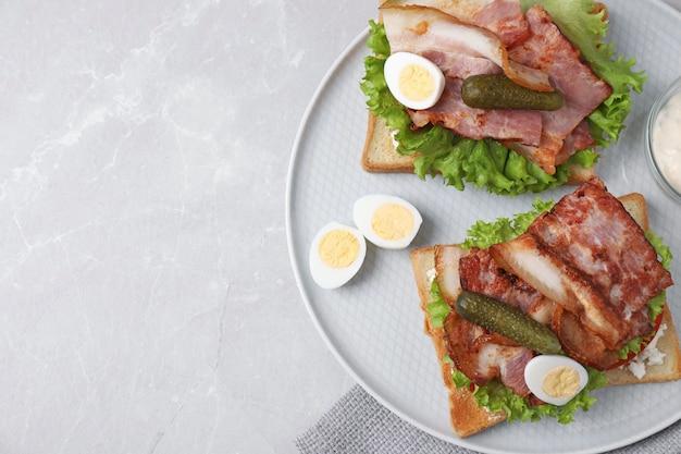 Вкусные бутерброды с беконом и перепелиными яйцами на светло-сером столе, вид сверху