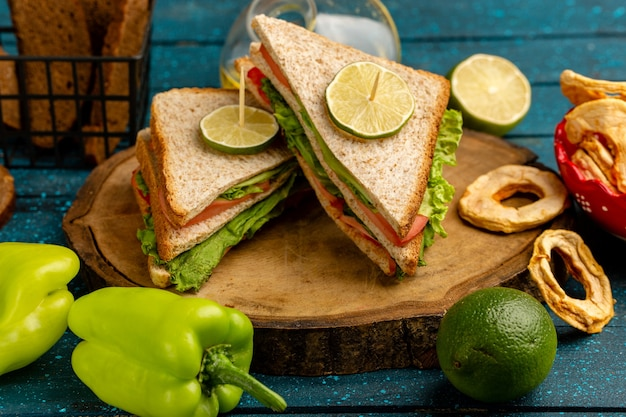 Tasty sandwiches with green salad tomatoes along with green bell-pepper bread and lemon on blue