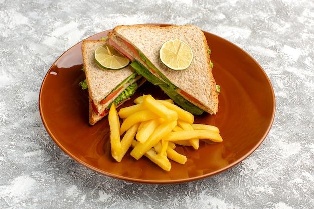 가벼운 책상에 갈색 접시 안에 그린 샐러드 토마토 감자 튀김과 맛있는 샌드위치
