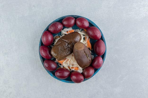 Crauti, melanzane e prugne saporiti sul piatto blu.