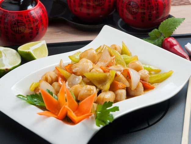 Tasty scallop with vegetables on a white plate chinese cuisine