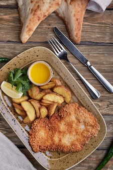 Tasty schnitzel with boiled potato. top view, flat lay food