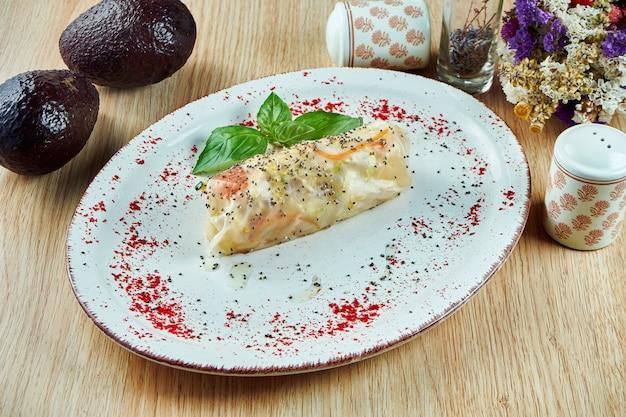 サーモン、ニンジン、ほうれん草の木製テーブルの上の青い皿においしいシーフード春巻き。タイの屋台。フィットネスと健康的な食事。閉じる。
