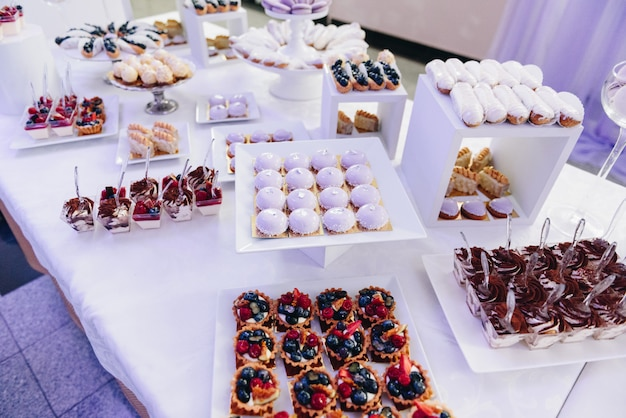 Tasty selection of delicious desserts, cakes, cupcakes and pastry on a buffet table at banquet