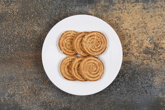 Вкусное печенье с семенами кунжута на белой тарелке.