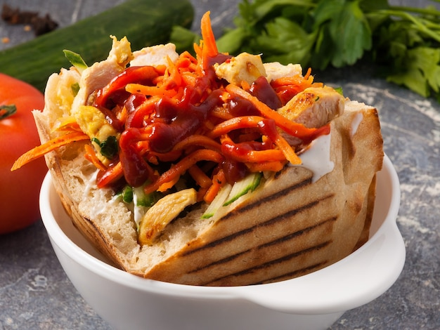 Tasty shawarma with chicken in a pit with carrots and ketchup.