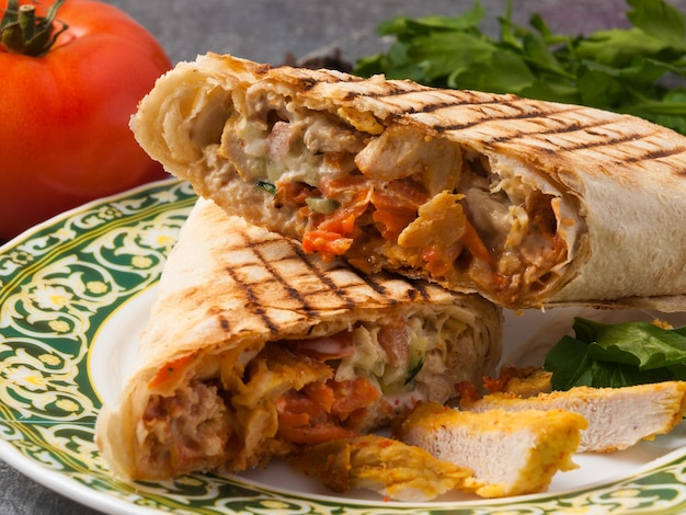 Tasty shawarma with chicken, vegetables and sauce. close up