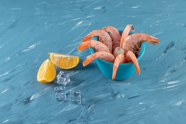 Tasty shrimps in a bowl next to lemons and ice cube, on the marble surface.