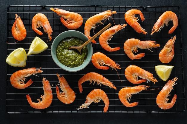Вкусные креветки со специями и соусом на борту на темном фоне. вид сверху.