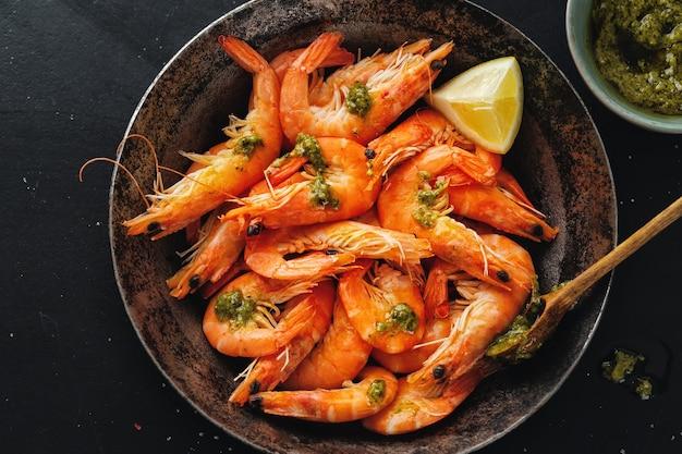 Вкусные креветки со специями и соусом на сковороде на темной поверхности