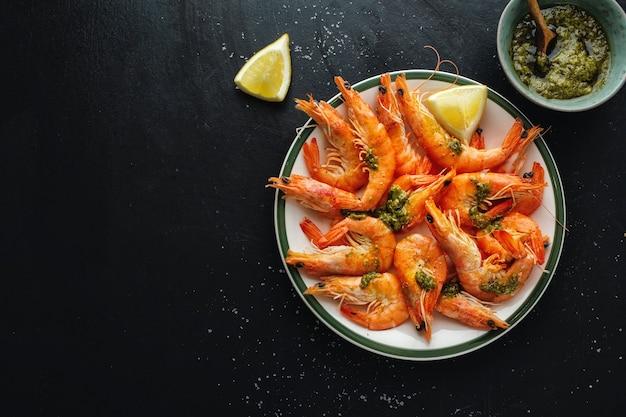 Вкусные креветки со специями и соусом на тарелке на темной поверхности