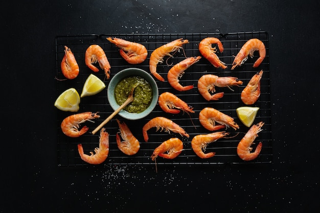 Tasty shrimps with spices and sauce on board on dark surface