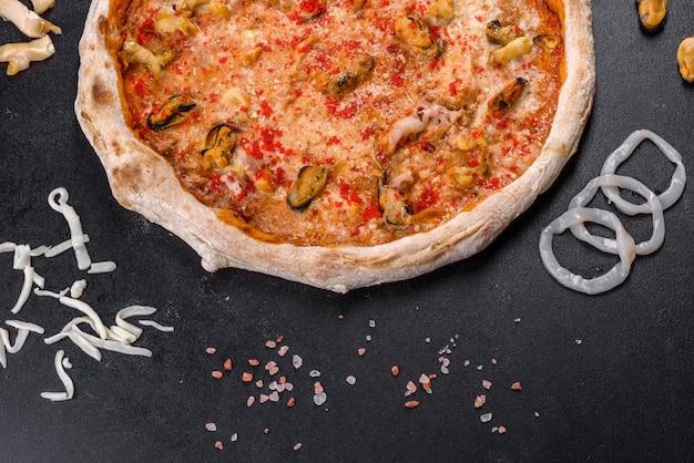黒の背景にシーフードとトマトのおいしいスライスピザ。地中海料理