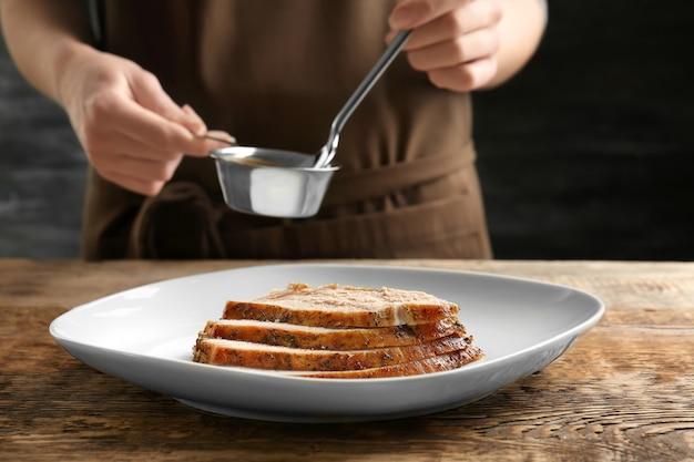 Вкусная нарезанная индейка на тарелке и шеф-повар с соусом в маленькой кастрюле за столом