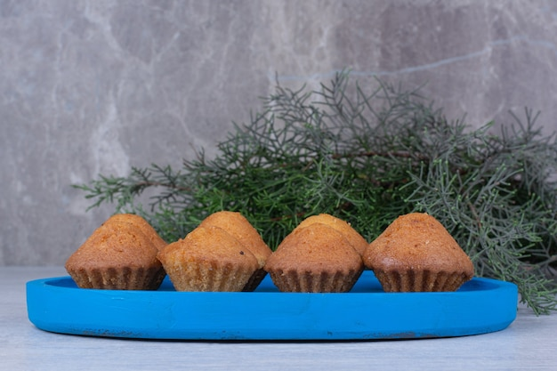 Tasty small cakes on blue plate with pine branch.