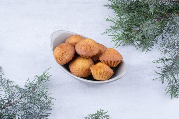 松の枝が付いているセラミックボウルのおいしい小さなケーキ。