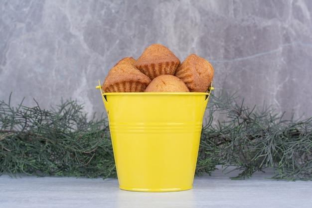 松の枝と黄色のバケツでおいしい小さなケーキ。