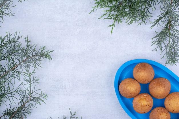 松の枝と青いプレート上のおいしい小さなケーキ