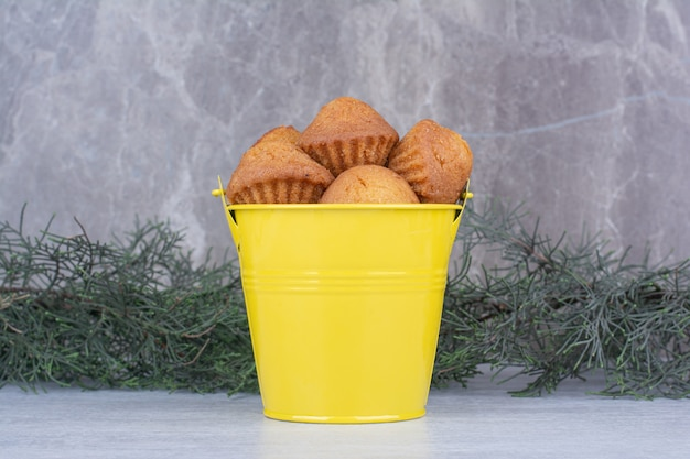 Tasty small cakes in yellow bucket with pine branch.