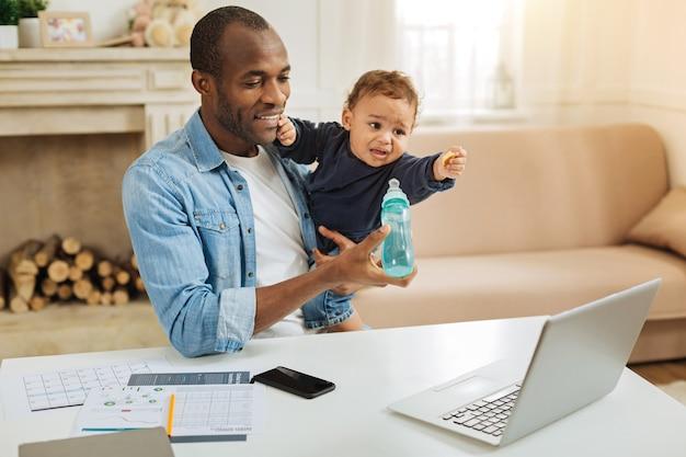 おいしい。彼の幼い息子を保持し、彼のラップトップでテーブルに座っている間彼を養う愛情のある若いアフリカ系アメリカ人の父の笑顔