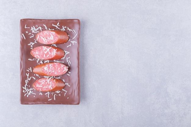 Salsicce affumicate saporite sul piatto marrone.