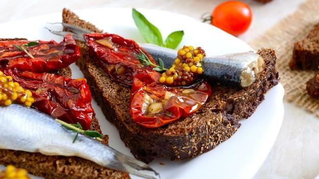 Вкусный сморреброд на белой тарелке. бутерброды с черным ржаным хлебом, вялеными помидорами, солеными анчоусами, горчицей.