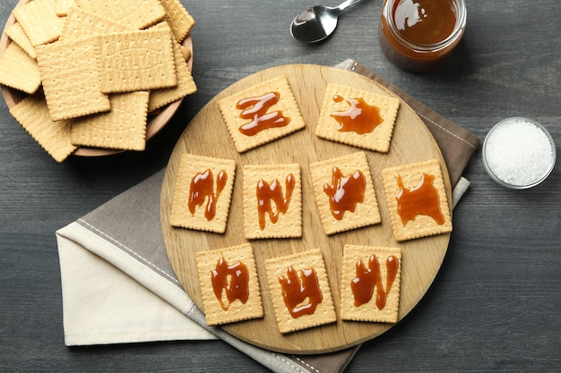 Концепция вкусной закуски с печеньем с карамелью на темном деревянном столе