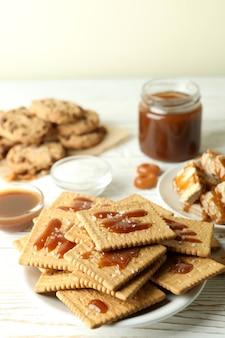 Концепция вкусной закуски с печеньем с карамелью на белом деревянном столе