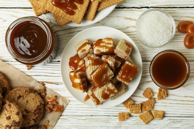 concetto di spuntino gustoso con i biscotti con caramello sul tavolo di legno bianco