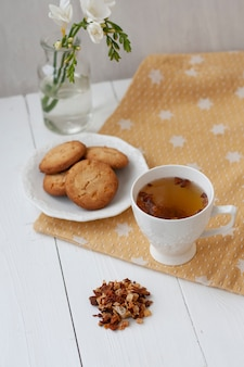 Tasty snack. cup of tea and a plate of cookies.