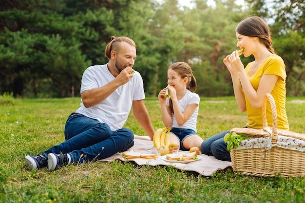 おいしいおやつ。太陽が降り注ぐ森の牧草地の草の上に座って、おいしいサンドイッチを食べている愛らしい若い家族