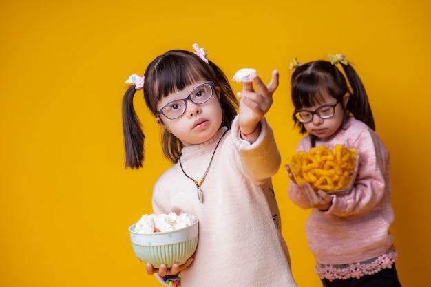 Вкусные закуски. необычно привлекательный ребенок показывает свою еду, пока сестра стоит сзади с миской зефира
