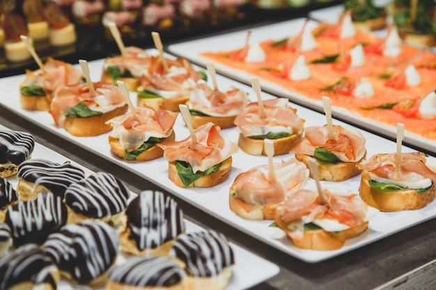 Tasty snacks with salted salmon and cottage cheese filling on square plate