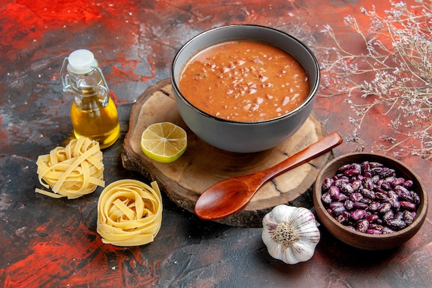木製トレイにスプーンとレモンを添えたディナーにおいしいスープ豆ガリックオニオンと他の製品を混合色のテーブルに
