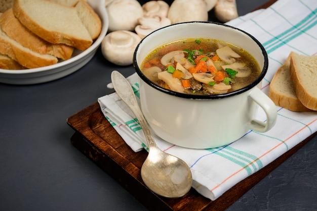Вкусный суп в сковороде над серой поверхностью. закройте